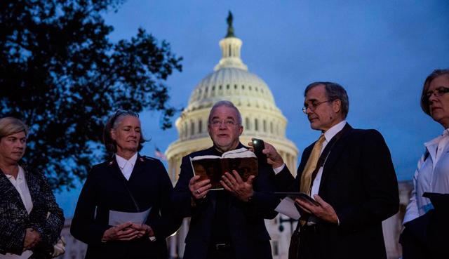 El reverendo Jim Wallis reza con un grupo de feligreses frente al Capitolio.  Afp