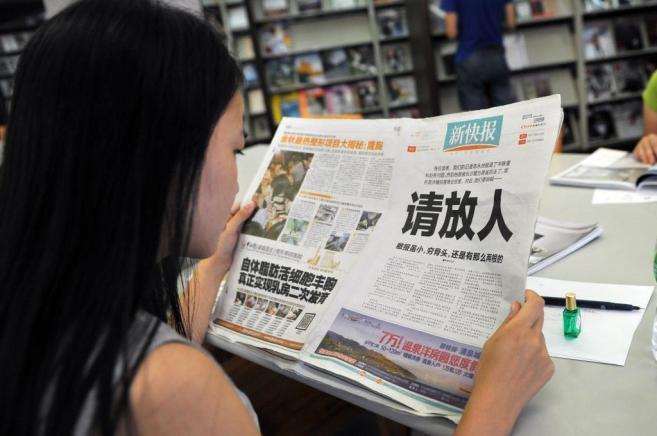 Una mujer lee un ejemplar del diario 'Xinkuaibao'