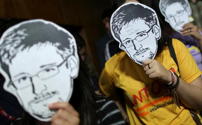 Varios jóvenes protestan en Brasilia con caretas de Edward Snowden.