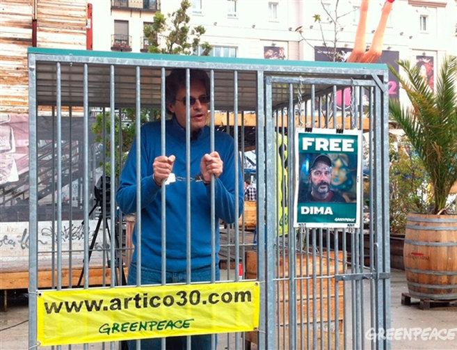 Un activista de Greenpeace en una jaula.