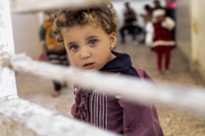 Una niña siria mira a la cámara a través de una alambrada
