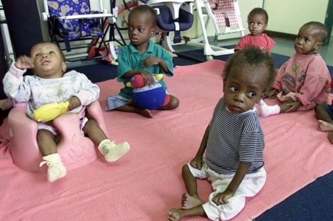 Varios niños sudafricanos juegan en el suelo