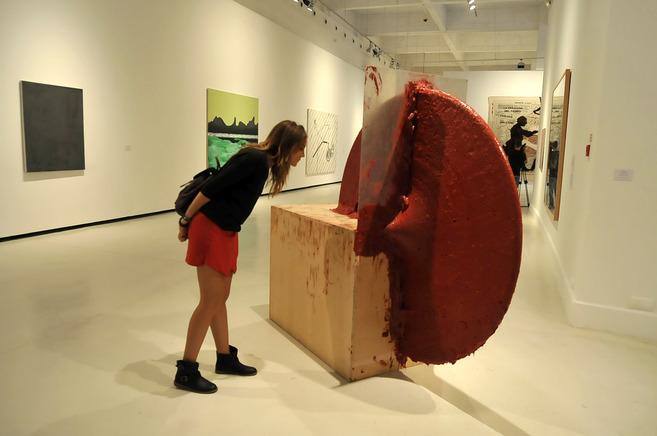 Una joven admira una escultura de Anish Kapoor.