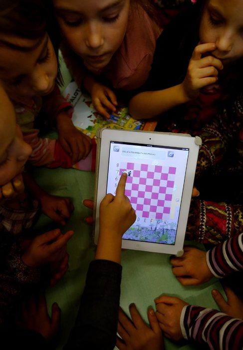 Varios niños observando la pantalla de una tableta