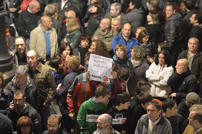 Manifestantes contra el cierre de Mondragón muestran un cartel sobre...