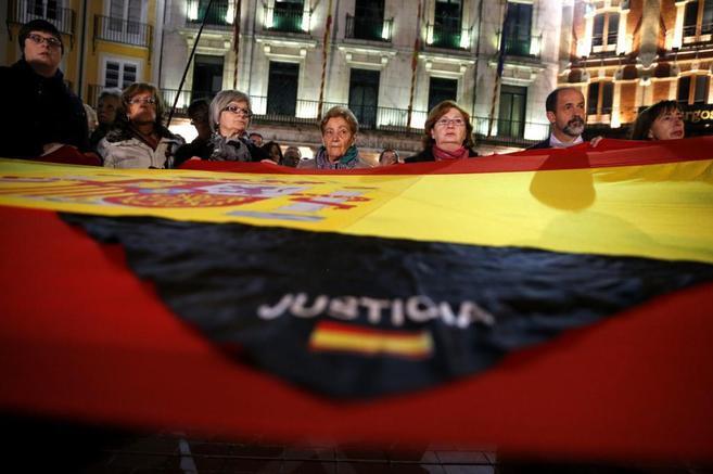 Bandera de España en primer plano, lleva una tela negra que dice...