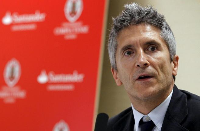 Retrato de Fernando Grande Marlaska, delante de una pantalla roja