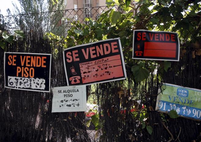 Varios carteles de 'Se vende' colgados en la entrada a una...