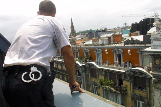 Vigilante de seguridad mira de la azotea de un edificio