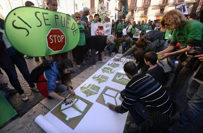 Activistas de la PAH, en camisas verdes, alrededor de un cartel de...