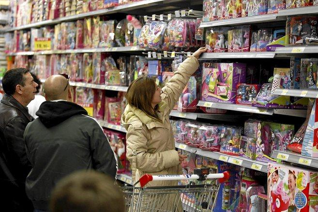 Consumidores escogiendo un juguete en un hipermercado en Navidad