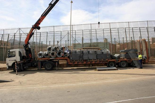 Camión con materiales de construcción en primer plano, delante un...