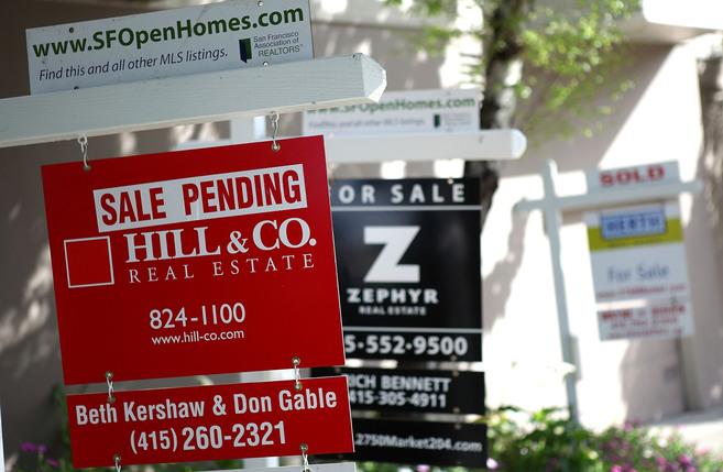 Varios carteles de inmobiliarias anuncian una casa en San Francisco.