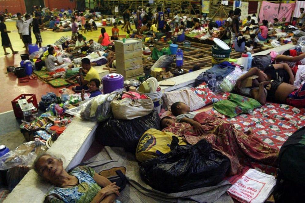 Multitud de filipinos se acuestan en el suelo de un gimnasio en la ciudad de Sorsogon.