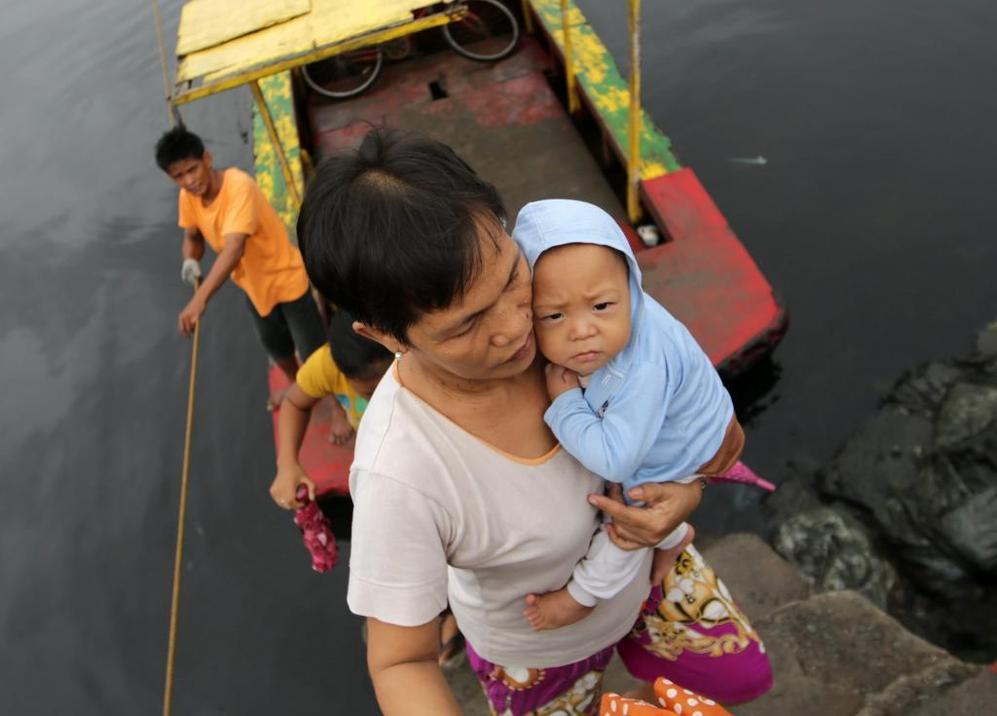 Una mujer atraviesa el río con su bebé en brazos en una aldea costera al sur de Manila.