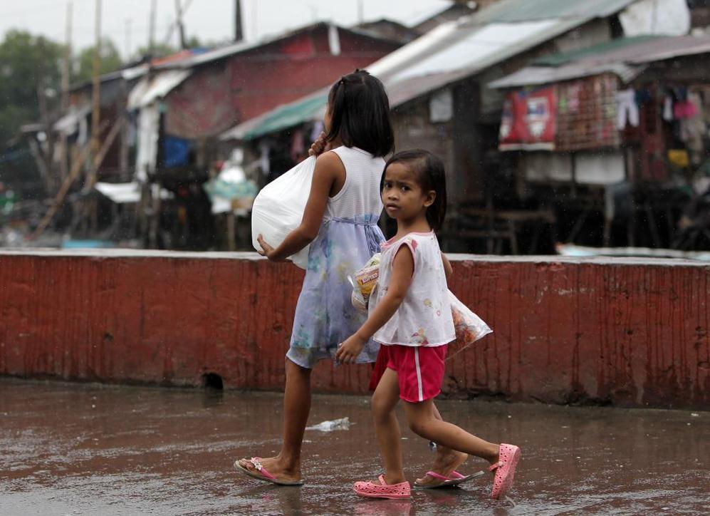 Unas niñas llevan provisiones en una aldea costera al sur de Manila.