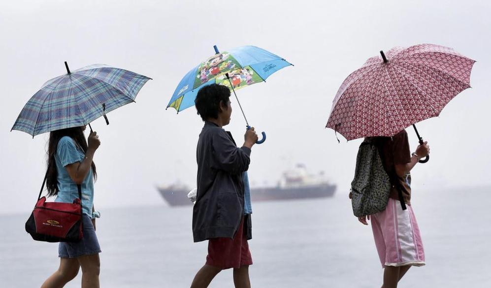 Tres mujeres pasean junto al mar en un día lluvioso a la llegada del tifón 'Haiyan' en Manila.