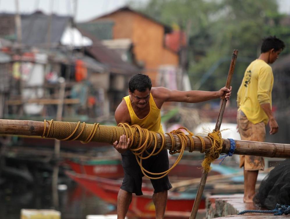 Un pescador filipino levanta un poste para reforzar su casa al sur de Manila.