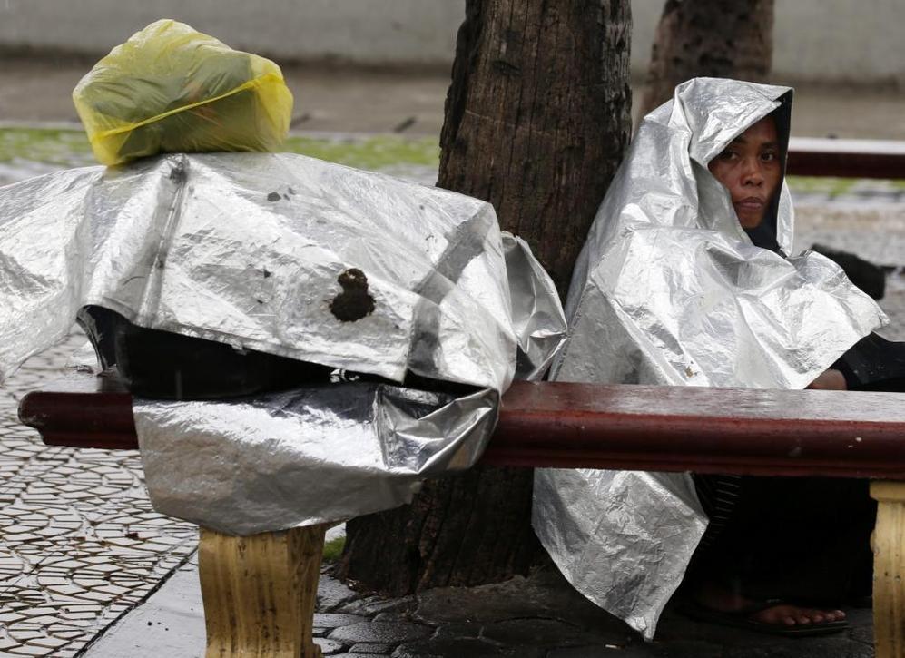 Una mujer se cubre con plásticos para refugiarse de la lluvia ala llegada del tifón 'Haiyan'.