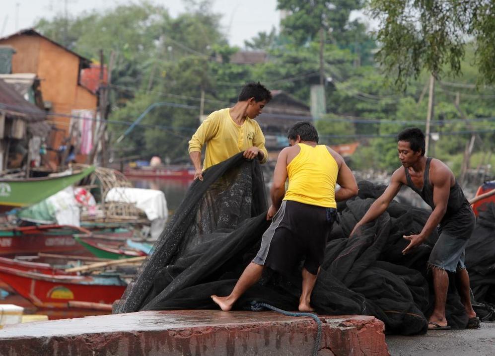 Pescadores filipinos levantan una red de pesca en una aldea al sur de Manila.