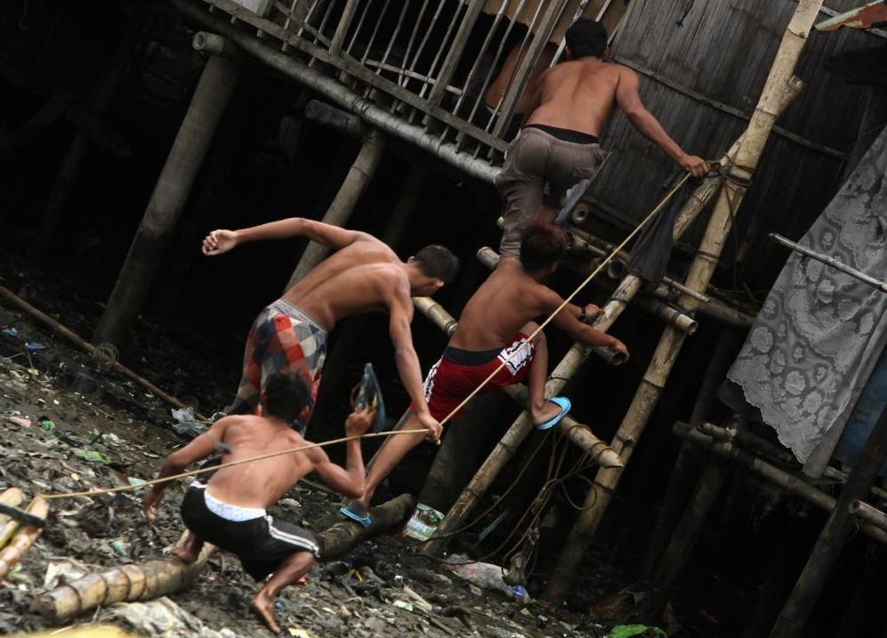 Unos residentes filipinos caminan sobre el barro en una aldea costera al sur de Manila.