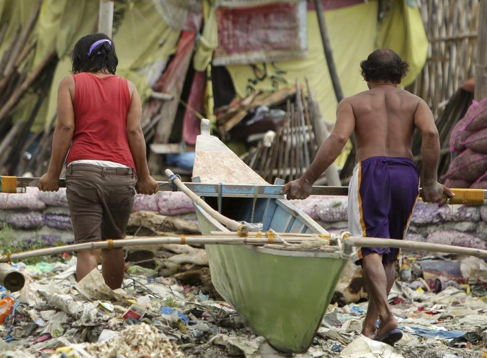 Una pareja pone una barca a resguardo en Manila.