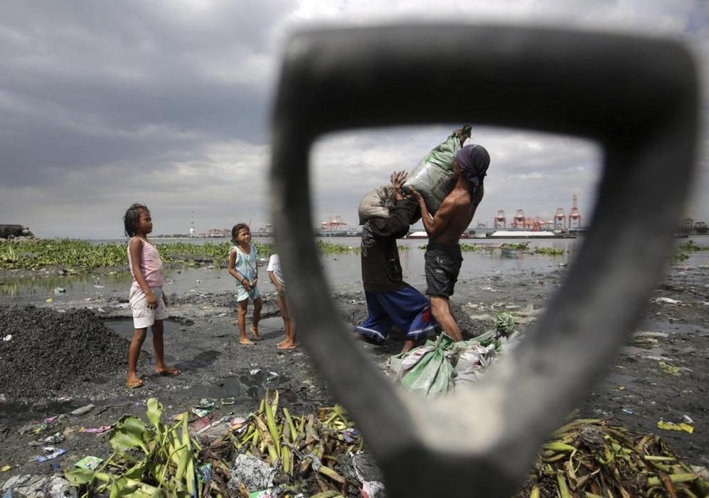 Dos hombres cargan sacos de arena y se preparan para la llegada del tifón Haiyan.