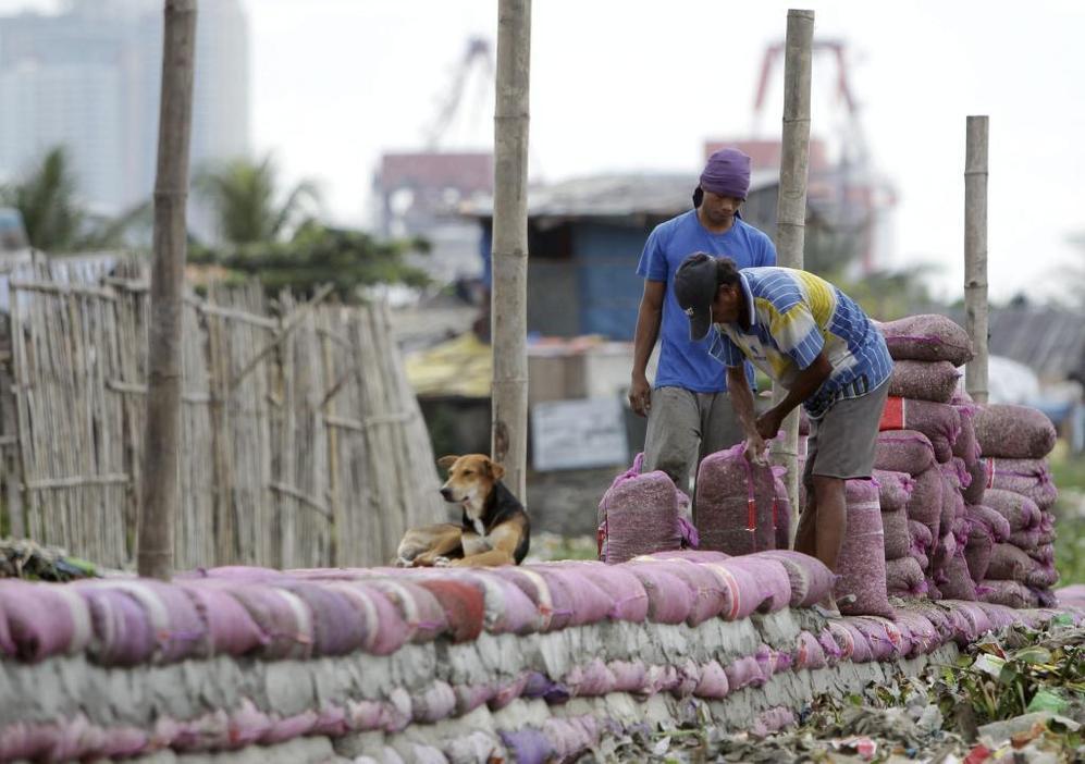 Dos hombres trabajan en la construcción de un dique con sacos de arena en Manila ante la previsión de un tifón.