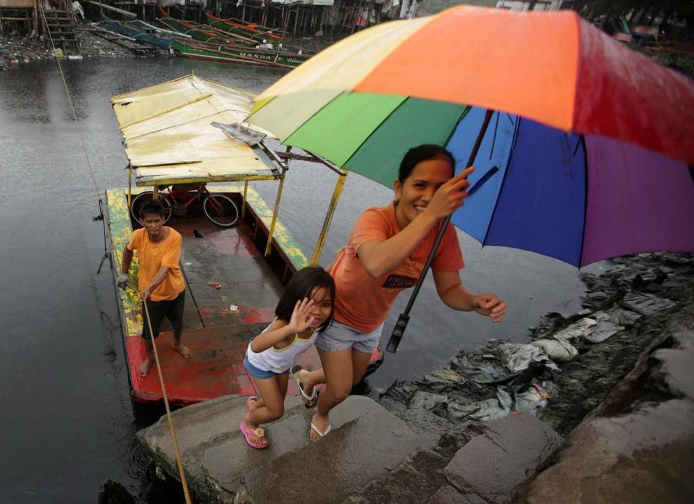 Unos residentes filipinos atraviesan un río ante la llegada del 'megatifón' 'Haiyan'.