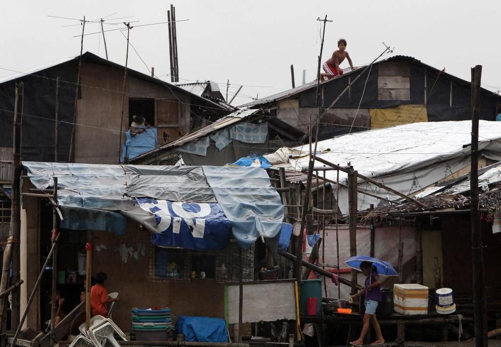 Residentes filipinos refuerzan sus viviendas ante la llegada del tifón 'Haiyan'.