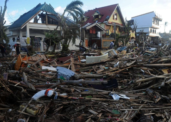 Residentes en Palo caminan entre las ruinas de las casas destruidas...