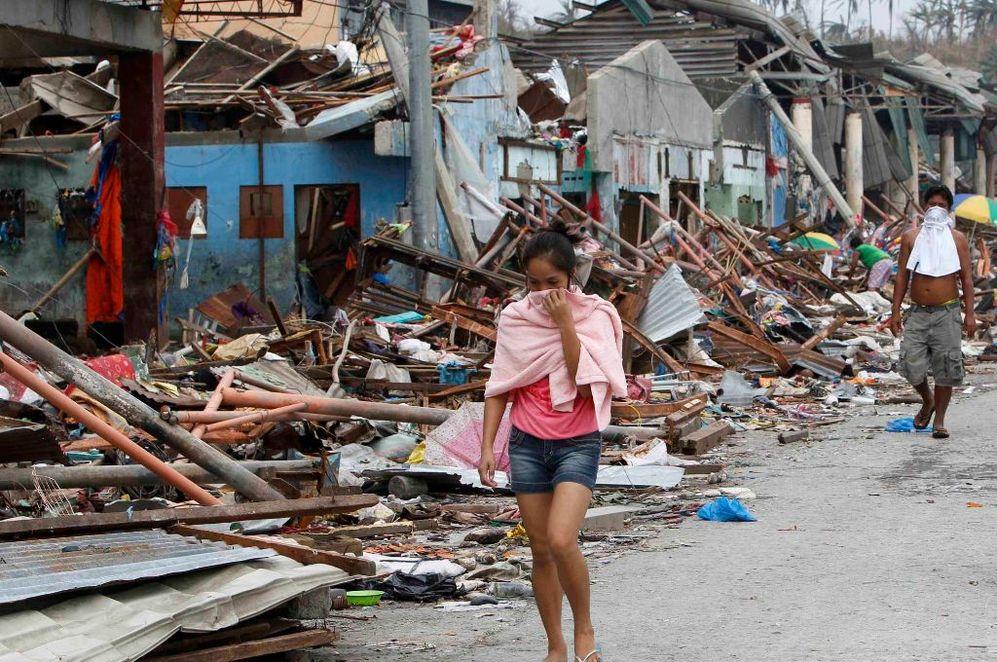Una joven se tapa la nariz tras pasar por las casas devastadas en Tacloban.