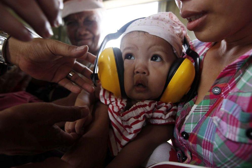 Una madre filipina protege con cascos a su bebé enfermo tras ser evacuados de Tacloban.
