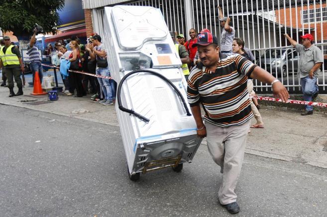 Un hombre porta un frigorífico ante una larga cola de venezolanos