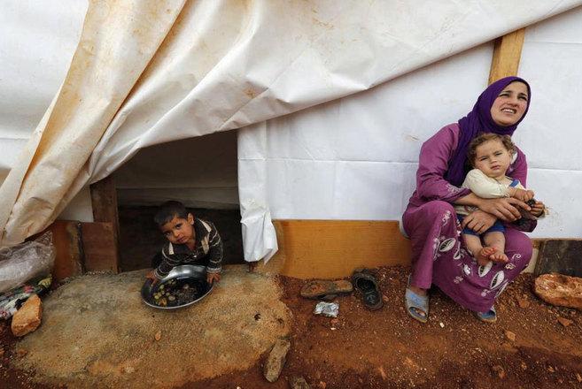 Una refugiada siria, con sus hijos en el campo de refugiados de Kfar...