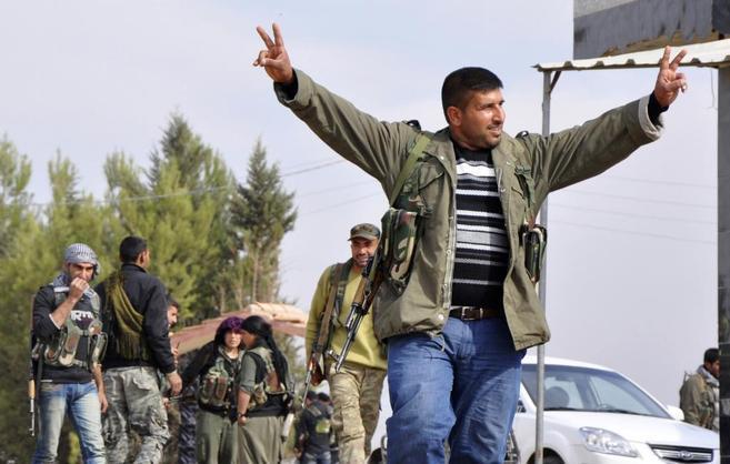 Un hombre kurdo hace el signo de la victoria en la ciudad de Ras...