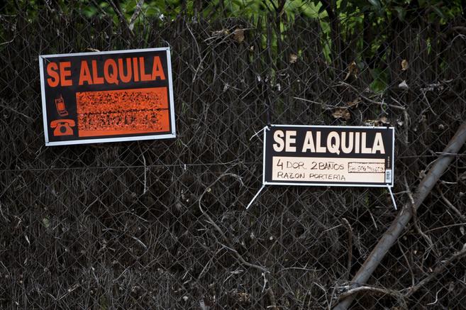 Dos carteles de 'Se alquila' colgados en la valla de una...