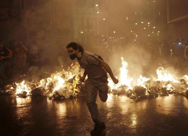 Un miembro del grupo llamado Black Bloc corre en Río de Janeiro.