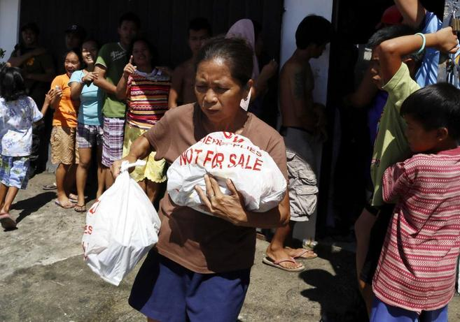 Una mujer cargada con bolsas de ayuda humanitaria.