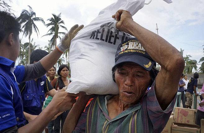 Un hombre carga con un saca con ayuda humanitaria, en Cebú.