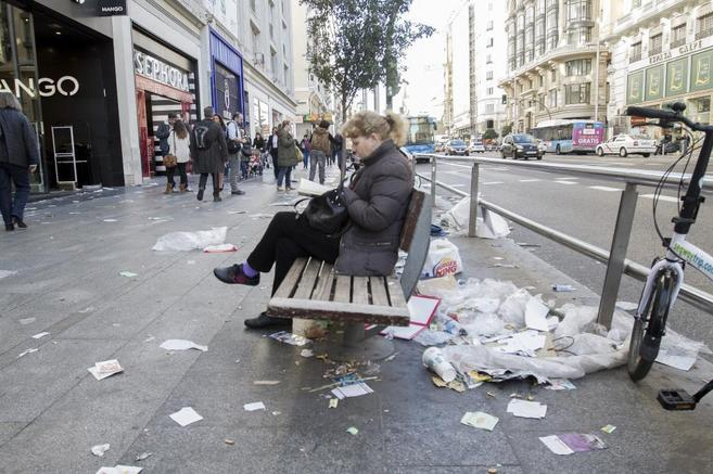 Una mujer lee en la Gran Vía rodeada de basura.