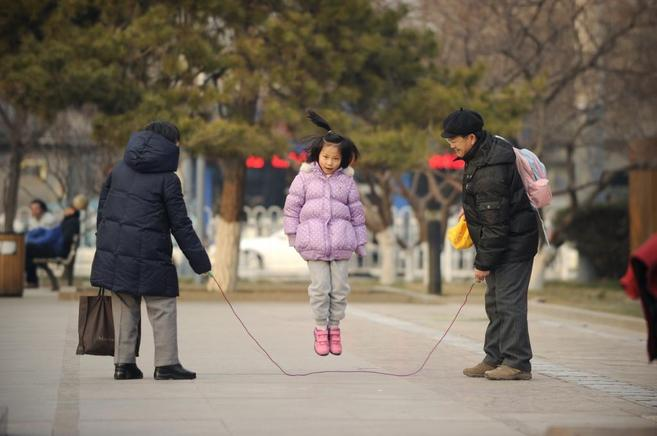 Una niña salta a la comba con sus padres, en Pekín.