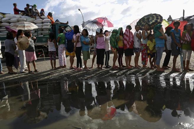 Supervivientes esperan en fila para recibir ayuda en Tacloban.