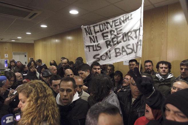 Trabajadores del servicio de limpieza muestran una pancarta de...
