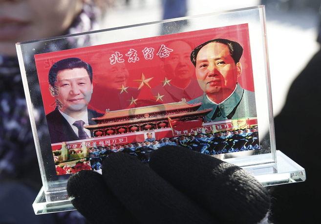 Un vendedor muestra un souvenir con el retrato de Xi y Mao.