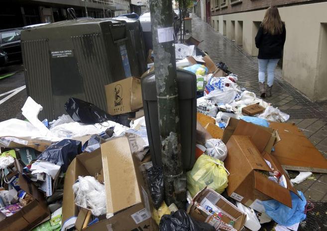 Basura sin recoger junto a varios contenedores de la calle de...