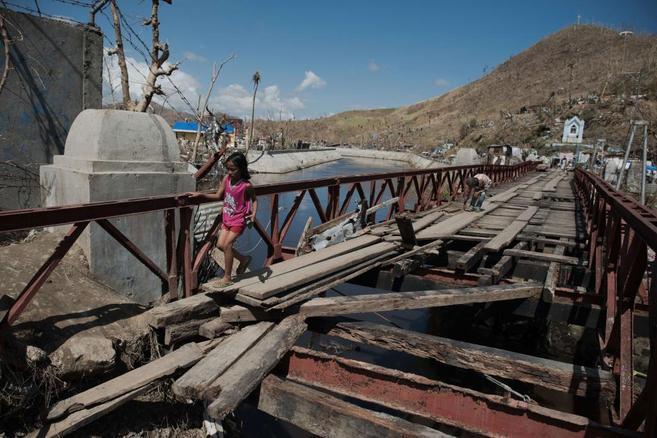 Una niña cruza un puente dañado por el tifón Haiyan