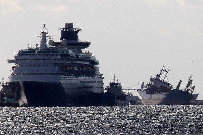 El mercante escorado, a la derecha, junto a un crucero en el puerto de...