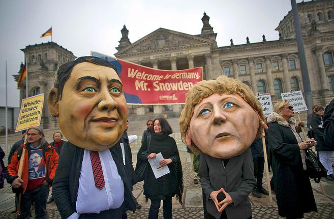 Activistas con máscaras de la canciller alemana (dcha.) y del líder...