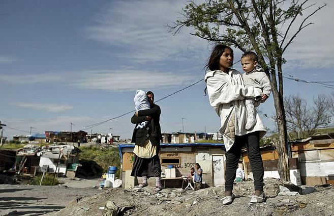 Dos mujeres, con sus hijos en un poblado clavolista en Madrid.